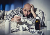 Sick man lying in bed suffering cold and winter flu virus having medicine and tablets — Stock Photo