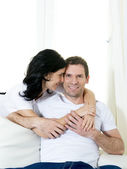 Attractive Brazilian couple with standing woman hugging his husband sitting in living room couch smiling happy in love concept — Stock Photo