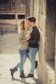 Candid portrait of beautiful European couple with rose in love kissing on street alley celebrating Valentines day — Stock Photo