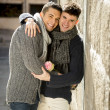 Young happy attractive gay men couple holding rose hugging and kissing outdoors Valentines free homosexual love — Stock Photo #64619735