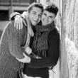 Young happy attractive gay men couple holding rose hugging and kissing outdoors Valentines free homosexual love — Stock Photo #64619853