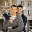Young happy gay men couple cuddling on street free homosexual love concept — Stock Photo #64622047
