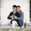 Young attractive gay men couple celebrating together Valentines day or anniversary champagne toast — Stock Photo #64624157