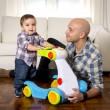 Young father and little son walking with baby walker taking his first brave steps — Stock Photo #64798103