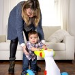 Young mother and little one year old son walking with baby walker taking his first brave steps — Stock Photo #64798413