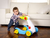 Sweet little boy playing alone with baby walker taking his first steps excited and playful — Stock Photo