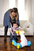 Young mother and little one year old son walking with baby walker taking his first brave steps — Stock Photo