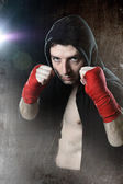 Man in boxing hoodie jumper with hood on head with wrapped hands wrists ready to fight — Stock Photo
