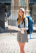 Happy attractive exchange student girl visiting Madrid city reading map — Stock Photo