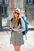 Happy attractive exchange student girl having fun in town visiting Madrid city reading tourist guide book — Stock Photo