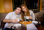 Young beautiful American tourist couple having spanish typical breakfast hot chocolate with churros smiling happy — Stock Photo