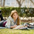 Young beautiful student girl on campus park grass with books studying happy preparing exam in education concept — Stock Photo #66001111