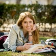 Young beautiful student girl on campus park grass with books studying happy preparing exam in education concept — Stock Photo #66002505