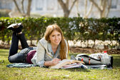 Young beautiful student girl on campus park grass with books studying happy preparing exam in education concept — ストック写真