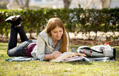 Young beautiful student girl on campus park grass with books studying happy preparing exam in education concept — Foto de Stock