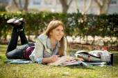 Young beautiful student girl on campus park grass with books studying happy preparing exam in education concept — Stock Photo