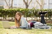 Young student girl lying on park grass with computer studying or surfing on internet — Stock Photo
