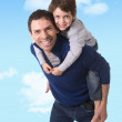 Young happy Brazilian father carrying on his back little son smiling and having fun together — Stock Photo #66755269