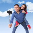 Attractive Brazilian father carrying cute young daughter on his back having fun smiling happy taking selfie photo with mobile phone — Stock Photo #66755319