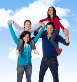 Young happy Brazilian mother and father playing with little son and daughter having fun all together outdoors on a blue sky — Stock Photo