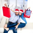 Young happy couple in Santa hat on Christmas holding shopping bags with presents  — Stock Photo #66954351