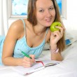 Young attractive student woman with apple in nightgown lying rel — Stock Photo #67982623