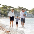 Young happy beautiful family walking together on the beach enjoying summer holidays — Stock Photo #70065671