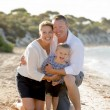 Beautiful family couple wife and husband holding little daughter on beach — Stock Photo #70619149
