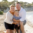 Beautiful family couple wife and husband holding little daughter on beach — Stock Photo #70619159