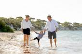 Young happy mother and father walking on beach in family vacation concept — Stock Photo