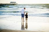 Happy father holding holding hand of little son walking together on the beach with barefoot — Stock Photo