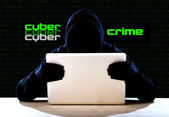 Hacker man in black hood and mask with computer laptop hacking system in digital intruder cyber crime concept — Stock Photo