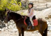 Sweet young girl 7 or 8 years old riding pony horse smiling happy wearing safety jockey helmet in summer holiday — Stock Photo