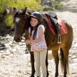 Young girl 7 or 8 years old holding bridle of little pony horse smiling happy wearing safety jockey helmet in summer holiday — Stock Photo #71550257