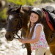 Young girl 7 or 8 years old holding bridle of little pony horse smiling happy wearing safety jockey helmet in summer holiday — Stock Photo #71550457