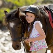 Young girl 7 or 8 years old holding bridle of little pony horse smiling happy wearing safety jockey helmet in summer holiday — Stock Photo #71550667