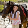 Young girl 7 or 8 years old holding bridle of little pony horse smiling happy wearing safety jockey helmet in summer holiday — Stock Photo #71550961