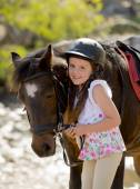 Young girl 7 or 8 years old holding bridle of little pony horse smiling happy wearing safety jockey helmet in summer holiday — Stock Photo
