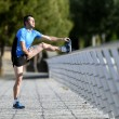 Athlete man stretching legs warming up calf muscles before running workout leaning on railing city urban park — Stock Photo #74658011