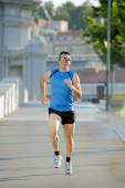 Young athletic man running on urban city park in summer sport training session — Stock Photo