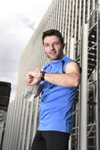 Young sport man checking time on chrono timer runners watch holding water bottle after training session — Stockfoto