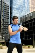 Young sport man checking time on chrono timer runners watch holding water bottle after training session — Stock Photo