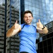Sport man doing victory winner thumbs up after running training in urban business district — Stock Photo #76078065