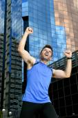 Attractive sport man doing victory and winner sign with his arms after running training in urban business district — Stock Photo