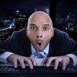 Businessman late at night in office typing on computer keyboard with funny face expression on watching porn online — Foto Stock #76461247