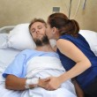 Couple at hospital room man lying in bed and woman holding his hand caring — Stock Photo #78243968