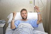 Angry patient man at hospital room lying in bed pressing nurse call button feeling nervous and upset — Stock Photo