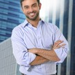 Attractive business man posing happy in corporate portrait outdoors on financial district — Stock Photo #79057018