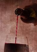 Man hand holding Bottle pouring red wine filling Glass on arty background — Stock Photo