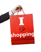 Man hand carrying and showing a red bag isolated on white background I love Shopping motto — Stock Photo